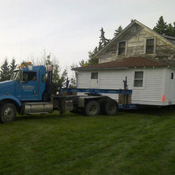 A muscular McConnell semi-tractor pulls a two-storey white house to it's new digs