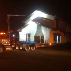 A McConnell Building Mover semi hauling a house on dollies in the night is illuminated by flood lamps.